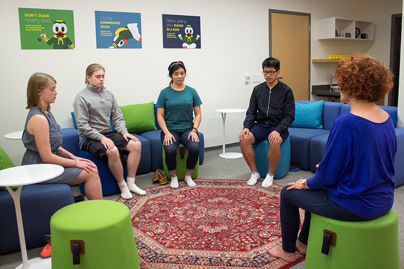 An instructor leads four students through a relaxation meditation in the Duck Nest.