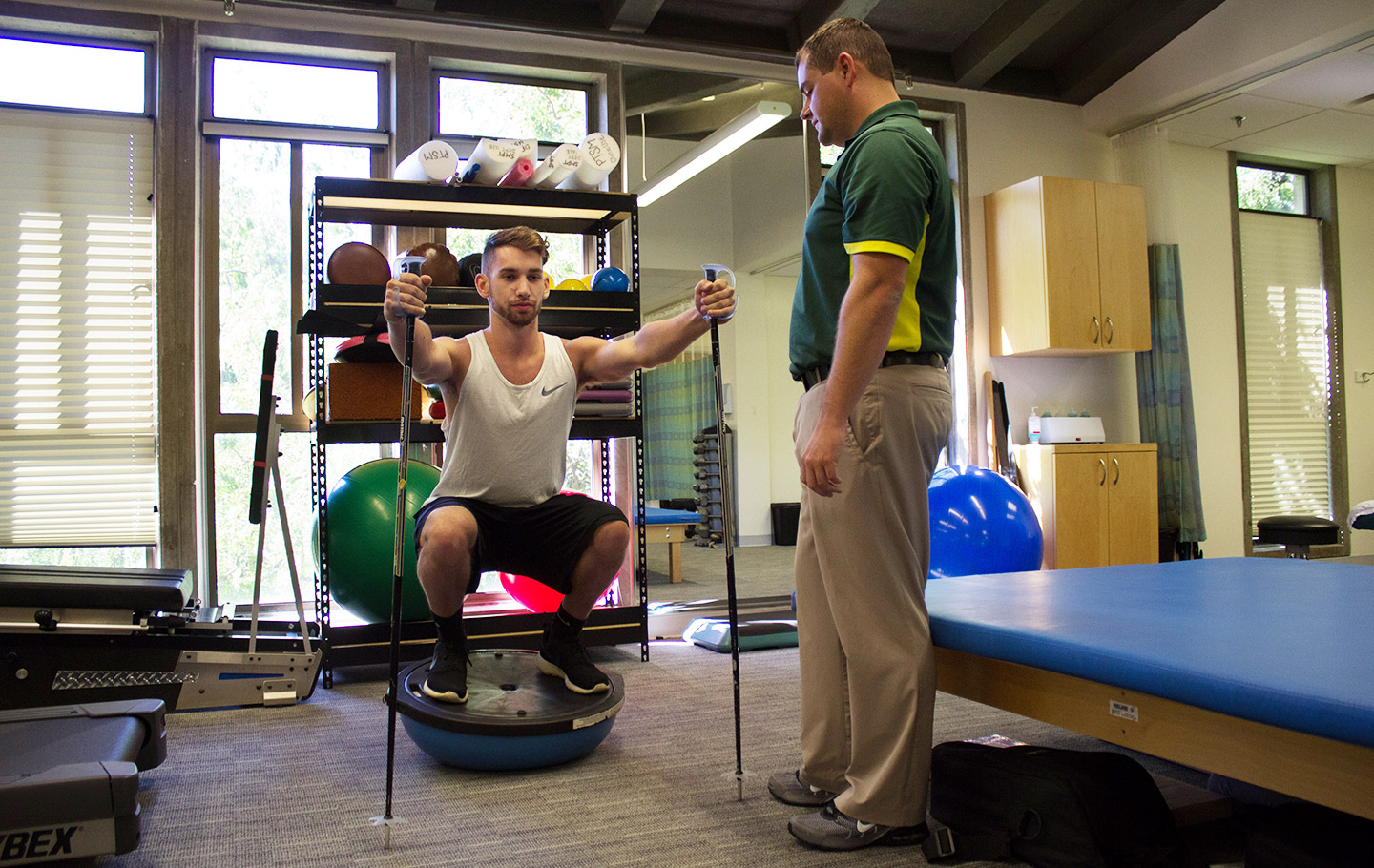 A student doing squats on a balance ball with a physical therapist advising him.
