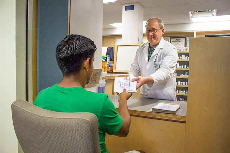 A student picking up a prescription from a pharmacist.