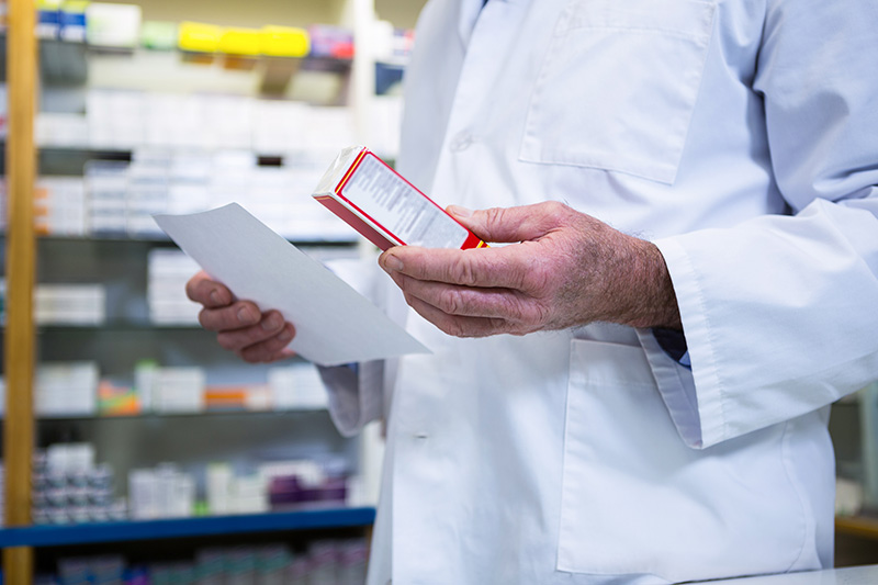 A pharmacist holds medicine and a prescription in his hand.